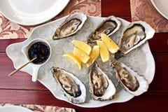 新鲜的牡蛎用说谎在盛肉盘和板材的柠檬作为纤巧 免版税库存照片