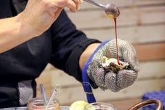 新鲜的牡蛎用调味汁在手上 库存照片