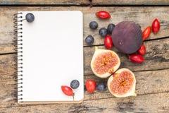 新鲜的狂放的莓果和无花果与空白的笔记本在木背景 图库摄影