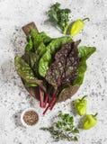 新鲜的瑞士牛皮菜、胡椒、硬花甘蓝、麝香草、牛至和香料在轻的背景 库存照片