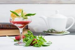 新鲜的甜草莓圆滑的人用在一个酒杯的薄菏在lig 免版税库存图片