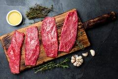 新鲜的生肉牛排 在木板,香料,草本,在蓝灰色的背景的油的牛里脊肉 烹调背景的食物 免版税库存照片