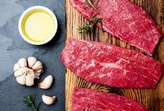 新鲜的生肉牛排 在木板,香料,草本,在蓝灰色的背景的油的牛里脊肉 烹调背景的食物 免版税图库摄影