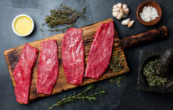 新鲜的生肉牛排 在木板,香料,草本,在蓝灰色的背景的油的牛里脊肉 食物烹调 库存照片