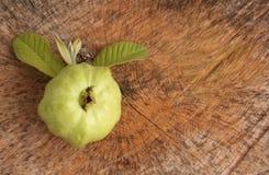新鲜的番石榴果子和叶子在木背景 库存图片