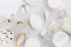 新鲜的白色自然化妆用品-在柔光白色木桌,平的位置上的白色奶油、油、毛巾和浴辅助部件 免版税库存图片