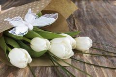 新鲜的白色郁金香和装饰蝴蝶花束  库存图片