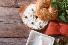 新鲜的百吉卷用乳酪、红色鱼和成份顶视图 免版税库存照片