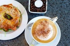 新鲜的百吉卷用沙拉和smodel钓鱼三文鱼和咖啡 早餐在咖啡馆或餐馆 库存照片