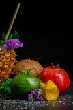 新鲜的石榴石、整个鲕梨和阳桃 逗人喜爱的花、椰子和菠萝 果子特写镜头在黑背景的 免版税库存照片