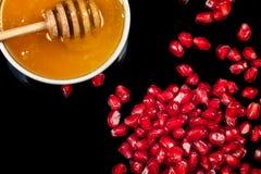 新鲜的石榴种子和蜂蜜在黑背景 图库摄影