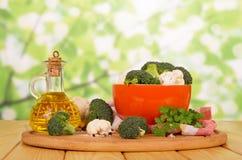 新鲜的硬花甘蓝、花椰菜和油在蒸馏瓶在抽象绿色 免版税库存照片