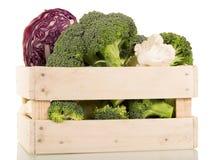 新鲜的硬花甘蓝、花椰菜和红叶卷心菜在被隔绝的木箱 免版税库存图片