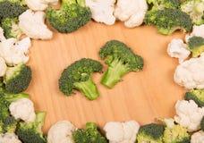 新鲜的硬花甘蓝和花椰菜在背景点燃木头 免版税图库摄影