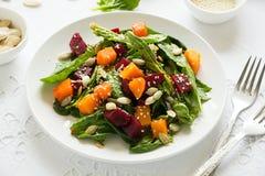 新鲜的秋天沙拉用用卤汁泡的南瓜和甜菜根、菠菜叶子、橄榄油、芝麻和南瓜籽在白色桌布 图库摄影