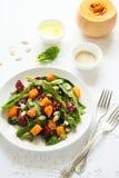 新鲜的秋天沙拉用用卤汁泡的南瓜和甜菜根、菠菜叶子、橄榄油、芝麻和南瓜籽在白色桌布 库存图片