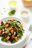 新鲜的秋天沙拉用用卤汁泡的南瓜和甜菜根、菠菜叶子、橄榄油、芝麻和南瓜籽 图库摄影