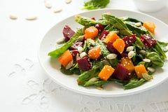 新鲜的秋天沙拉用用卤汁泡的南瓜和甜菜根、菠菜叶子、橄榄油、芝麻和南瓜籽 免版税库存图片