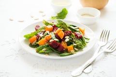 新鲜的秋天沙拉用用卤汁泡的南瓜和甜菜根、菠菜叶子、橄榄油、芝麻和南瓜籽 免版税图库摄影