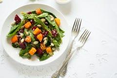 新鲜的秋天沙拉用用卤汁泡的南瓜和甜菜根、菠菜叶子、橄榄油、芝麻和南瓜籽 库存图片