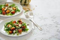 新鲜的秋天沙拉用被烘烤的南瓜、芝麻菜、乳酪和种子在白色桌布 图库摄影
