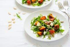 新鲜的秋天沙拉用被烘烤的南瓜、芝麻菜、乳酪和种子在白色桌布 免版税库存照片
