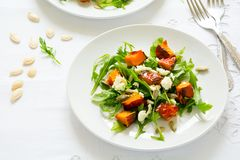 新鲜的秋天沙拉用被烘烤的南瓜、芝麻菜、乳酪和种子在白色桌布 免版税库存图片