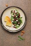 新鲜的素食主义者饮食沙拉用甜菜根、芝麻菜、希腊白软干酪、坚果和种子在棕色石背景 顶视图,平的位置 库存图片
