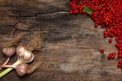 新鲜的红浆果莓果和大蒜在老木背景 免版税库存照片