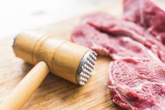 新鲜的红肉和一把锤子打的肉的 免版税库存图片