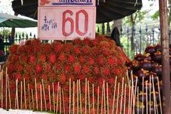 新鲜的红色红毛丹特写镜头在一个地方街道食物市场chatuchak市场上的在泰国,亚洲 免版税图库摄影