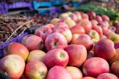 新鲜的红色苹果和菜在一个室外市场上 免版税库存照片