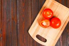 新鲜的红色蕃茄和被切的一半与香菜在一张木桌上 顶视图 免版税库存照片