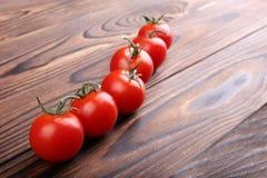 新鲜的红色蕃茄特写镜头  在木背景的五颜六色的蕃茄 有机沙拉成份 红色蕃茄 库存照片