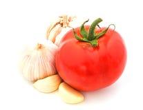 新鲜的红色蕃茄用在白色背景隔绝的大蒜 免版税库存图片