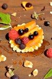 新鲜的红色,黑树莓和无核小葡萄干,桃子,在奶蛋烘饼的蜂蜜下落在木背景关闭 库存图片
