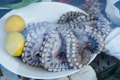 新鲜的结冰的章鱼用在白色板材的柠檬 免版税图库摄影