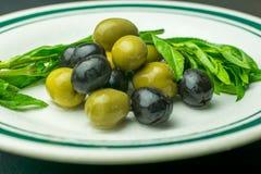 新鲜的绿色和黑橄榄,在一块白色瓷板材服务 免版税库存照片