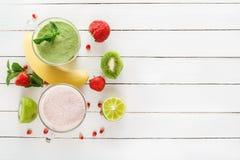 新鲜的绿色圆滑的人和草莓奶昔在玻璃玻璃的用在白板的热带水果 免版税库存照片
