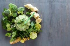 新鲜的绿色圆滑的人用荷兰芹、姜、硬花甘蓝、香蕉、石灰、黄瓜和薄菏在一块玻璃在一张黑木桌上 图库摄影