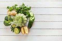 新鲜的绿色圆滑的人用荷兰芹、姜、苹果、石灰、黄瓜、硬花甘蓝和薄菏在一块玻璃在白板 库存图片
