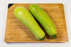 新鲜的绿色夏南瓜两个片断在一个木板说谎 库存照片