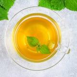 新鲜的绿色荨麻和一个清楚的玻璃杯子叶子在一张灰色具体桌上的草本荨麻茶 顶视图 库存图片