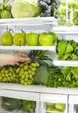 新鲜的绿色蔬菜和水果在冰箱 妇女采取束从开放冰箱的绿色葡萄 库存照片