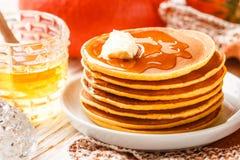 新鲜的自创南瓜薄煎饼用蜂蜜和黄油在一块白色板材 库存图片