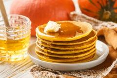 新鲜的自创南瓜薄煎饼用蜂蜜和黄油在一块白色板材 图库摄影