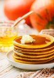 新鲜的自创南瓜薄煎饼用蜂蜜和黄油在一块白色板材 免版税库存图片