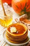 新鲜的自创南瓜薄煎饼用蜂蜜和黄油在一块白色板材 免版税库存照片