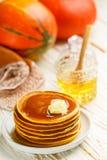 新鲜的自创南瓜薄煎饼用蜂蜜和黄油在一块白色板材 免版税图库摄影