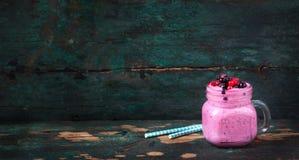 新鲜的自创在一个玻璃瓶子的酸奶圆滑的人野生野生莓果在老葡萄酒背景 免版税库存照片